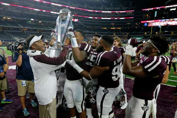 Texas A&M head coach Kevin Sumlin turns  the Southwest Classic trophy to his players after their win against Arkansas in an NCAA college football game, Saturday, Sept. 24, 2016, in Arlington, Texas. (AP Photo/Tony Gutierrez)