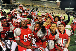 Members of the Cy Lakes football team celebrate after breaking the program record for wins in a season by defeating Cy Falls on Saturday night, Sept. 24, 2016.