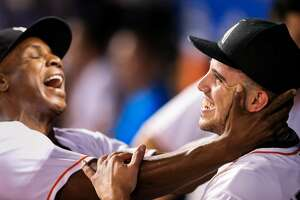 MIAMI, FL - SEPTEMBER 20: Jose Fernandez #16 of the Miami Marlins celebrates in the dugout with hitting coach Barry Bonds during the game against the Washington Nationals at Marlins Park on September 20, 2016 in Miami, Florida. (Photo by Rob Foldy/Getty Images)