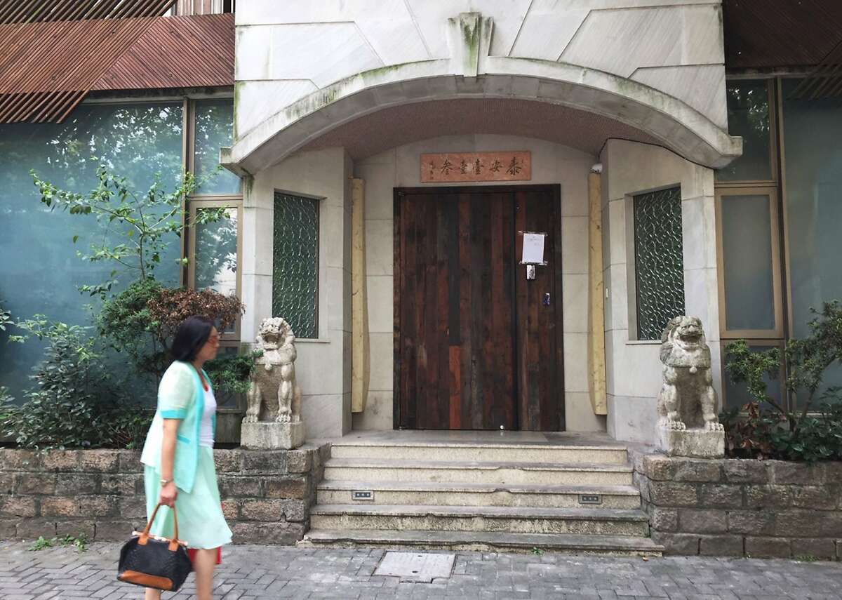 A woman walks past the closed Taian Table restaurant in Shanghai on September 23, 2016.