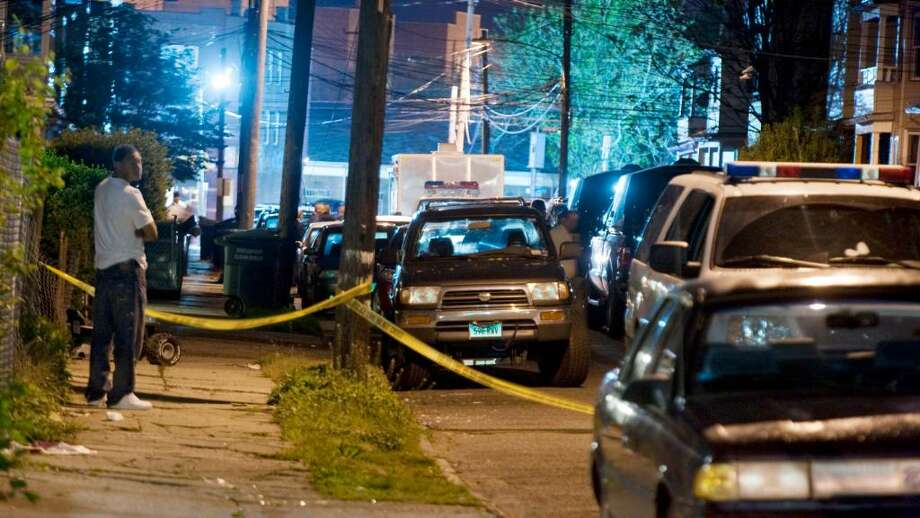 Police vehicles fill a street  early Tuesday morning May 4, 2010 as they  search  a home the center of the block in Bridgeport Conn.  An arrest in the Times Square bombing was made at Kennedy Airport in New York and local, federal and state officials are searching a residence in Bridgeport. Photo: Douglas Healey, AP / AP2010