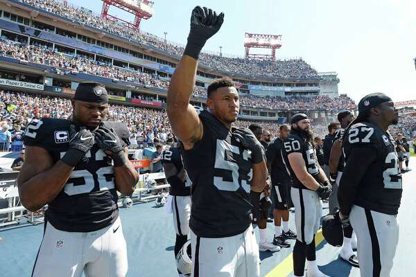 Oakland Raiders outside linebacker Malcolm Smith (53) raises a fist during the playing of the national anthem before an NFL football game against the Tennessee Titans Sunday, Sept. 25, 2016, in Nashville, Tenn. At left is defensive end Khalil Mack (52) and at right is free safety Reggie Nelson (27).