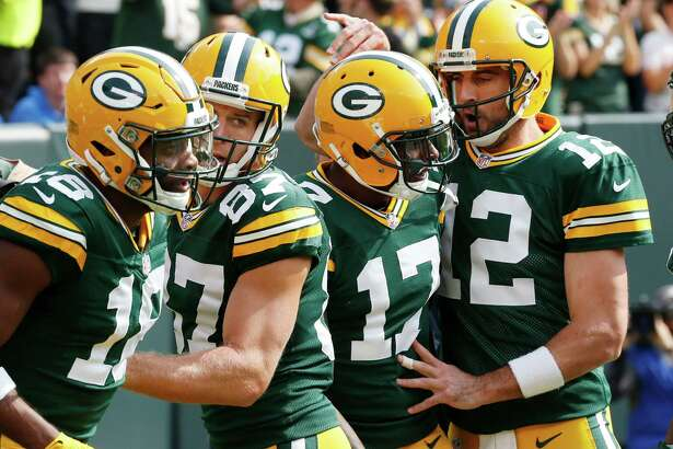 Green Bay Packers' Aaron Rodgers (12) congratulates wide receiver Davante Adams (17) after his touchdown catch during the first half of an NFL football game against the Detroit Lions Sunday, Sept. 25, 2016, in Green Bay, Wis.