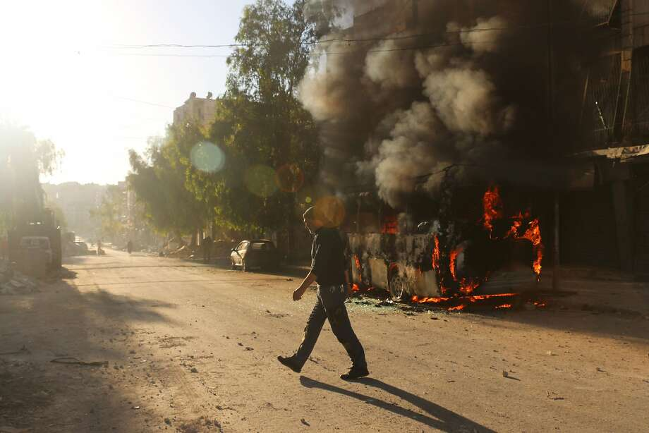 A Syrian man walks past a bus set ablaze following a reported air strike in the rebel-held Salaheddin district of Aleppo on September 25, 2016. The UN Security Council met for urgent talks as Syrian and Russian warplanes pounded rebel-held east Aleppo in the worst surge of bombing to hit the devastated city in years. Britain, France and the United States called the emergency meeting to turn up pressure on Russia and press demands that it rein in its ally Syria to halt the intense bombing campaign on Aleppo. / AFP PHOTO / AMEER ALHALBIAMEER ALHALBI/AFP/Getty Images Photo: AMEER ALHALBI, AFP/Getty Images