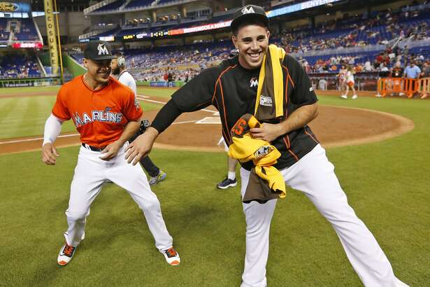 Miami Marlins right fielder Giancarlo Stanton, left, and pitcher Jose Fernandez play around after having received their All-Star Game jerseys during a ceremony on the field before the start of a baseball game against the Cincinnati Reds, Sunday, July 10, 2016, in Miami. (AP Photo/Wilfredo Lee)