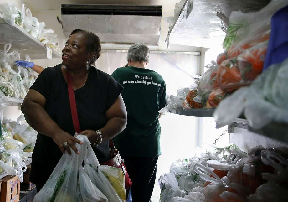 Carmelita Dorsey looks at fresh fruits and vegetables last week inside a refrigerator truck provided by the Greater Chicago Food Depository at the Oak Forest Health Center. Photo: Tae-Gyun Kim, Associated Press