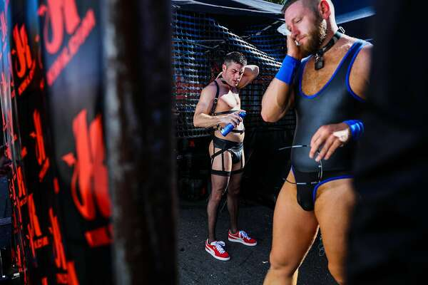 Lance Hart (center) applies sunscreen before making his way through  the Folsom Street Fair in San Francisco, California, on Sunday, Sept. 25, 2016.