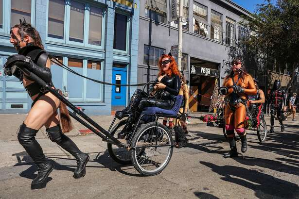 People dressed in costume walk through the Folsom Street Fair in San Francisco, California, on Sunday, Sept. 25, 2016.