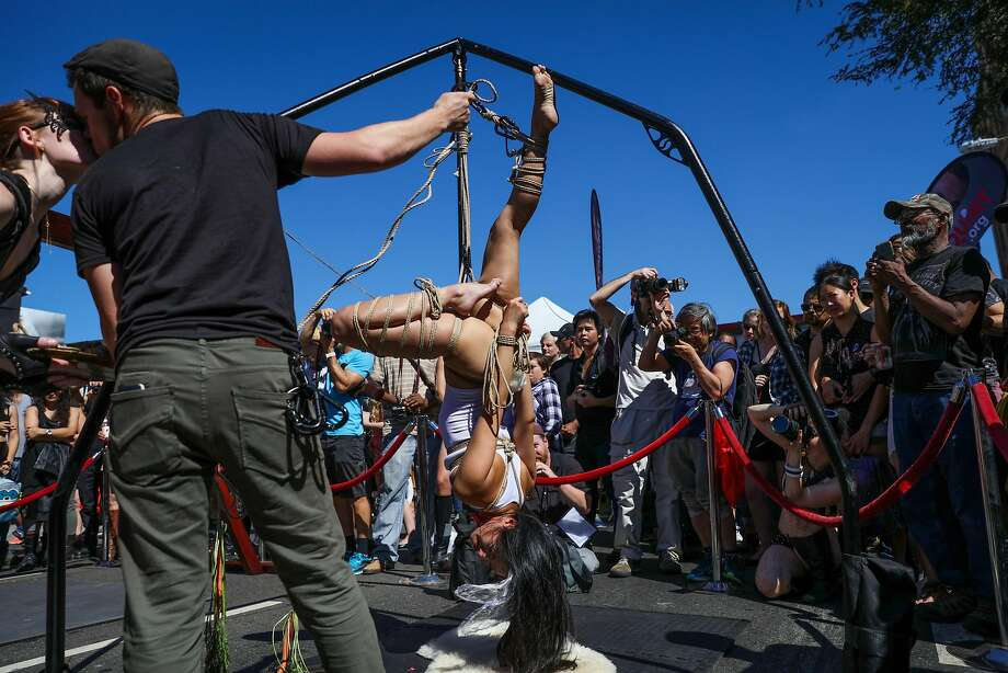 A couple shares a kiss, while a woman tied up in ropes hangs from an apparatus, at the Folsom Street Fair in San Francisco, California, on Sunday, Sept. 25, 2016. Photo: Gabrielle Lurie, The Chronicle