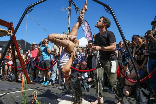 A woman tied up in ropes hangs from an apparatus, at the Folsom Street Fair in San Francisco, California, on Sunday, Sept. 25, 2016.