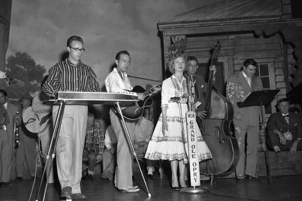 UNITED STATES - CIRCA 1956: Jean Shepard performs on the Grand Ole Opry with band and Webb Pierce (standing at music stand), in background, c. 1956. Don Helms front left on steel. Duke of Paducah (Whitey Ford) seated at far right. (Photo by Elmer Williams/Country Music Hall of Fame and Museum/Getty Images)