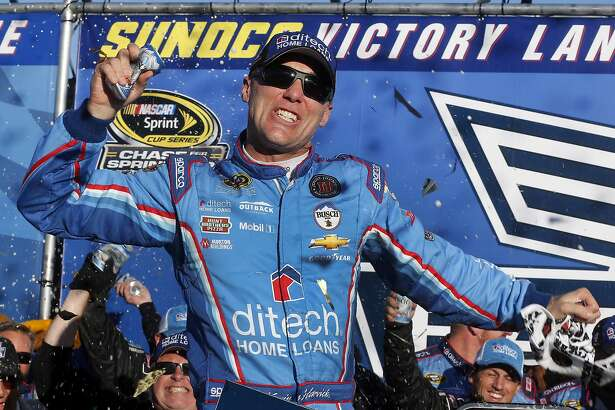 Kevin Harvick celebrates in Victory Lane after winning the NASCAR Sprint Cup Series auto race at New Hampshire Motor Speedway, Sunday, Sept. 25, 2016, in Loudon, N.H. (AP Photo/Jim Cole)
