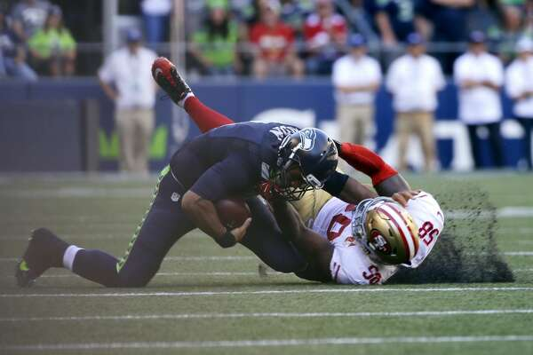 Seattle Seahawks quarterback Russell Wilson is pulled down by San Francisco 49ers' Eli Harold in the second half of an NFL football game, Sunday, Sept. 25, 2016, in Seattle. (AP Photo/Ted S. Warren)