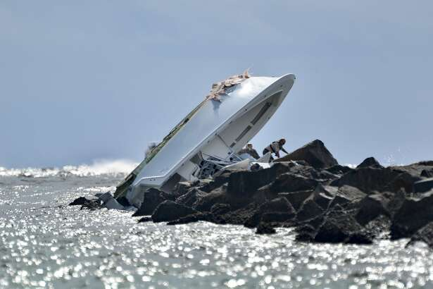 Investigators inspect an overturned boat as it rests on a jetty after a crash, Sunday, Sept. 25, 2016, off Miami Beach, Fla. Authorities said that Miami Marlins starting pitcher Jose Fernandez was one of three people killed in the boat crash early Sunday morning. He was 24. (AP Photo/Gaston De Cardenas)
