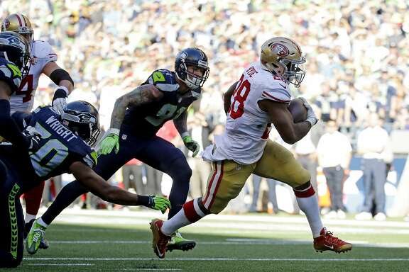 San Francisco 49ers' Carlos Hyde, right, scores a touchdown against the Seattle Seahawks in the second half of an NFL football game, Sunday, Sept. 25, 2016, in Seattle. (AP Photo/Ted S. Warren)