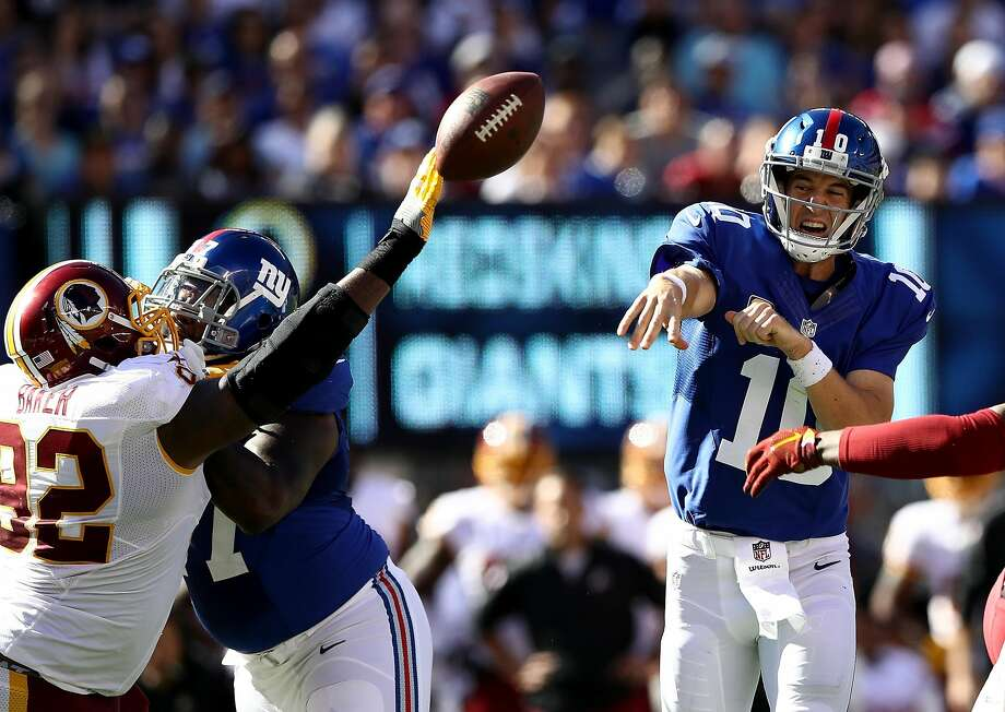 New York Giants quarterback Eli Manning's pass is batted away by Washington's Chris Baker. Photo: Elsa, Getty Images