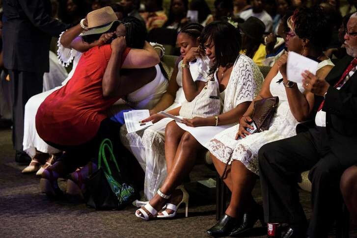 A row of family members sob and are embraced by friends during the funeral for Melvin McKinney, the last of four prisoners who committed suicide in the Bexar County Jail, at True Vision Church on August 2, 2016.
