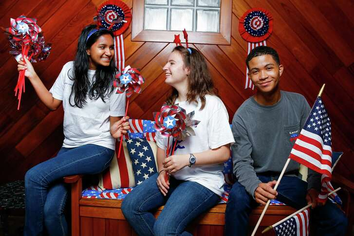 Lamar High School Young Democrats vice president Lekha Sunder, left, president Dikla Taylor, center, and Young Republicans president Noah Scantlebury have their props ready for the presidential debate watch party at the school cafeteria Monday night.