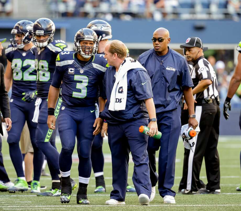 Seahawks quarterback Russell Wilson speaks with trainers after injuring his knee in Seattle's matchup with the San Francisco 49ers at CenturyLink Field in Seattle on September 25, 2016. The Seahawks won 37-18. (Photography by Scott Eklund/Red Box Pictures) Photo: Scott Eklund/Red Box Pictures