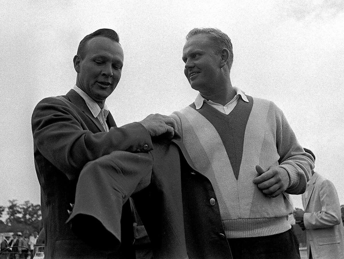 FILE -- Arnold Palmer, left, 1966 Masters champion, helps Jack Nicklaus into the traditional green jacket after Nicklaus' nine-stroke victory at Augusta National Golf Club, in this April 11, 1965 photo. (AP Photo/File)