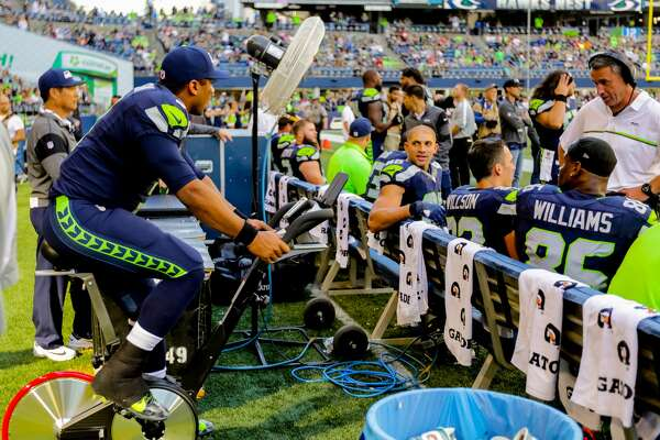 Russell Wilson stays loose after injuring his kneed during The Seattle Seahawks defeat the San Francisco 49ers 37-18 at CenturyLink  Field in Seattle on September 25, 2016. (Photography by Scott  Eklund/Red Box Pictures)