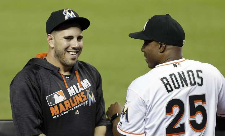 Miami Marlins' Jose Fernandez, left, talks to hitting coach Barry Bonds (25) in the dugout before a baseball game against the Atlanta Braves, Thursday, Sept. 22, 2016, in Miami. (AP Photo/Alan Diaz)