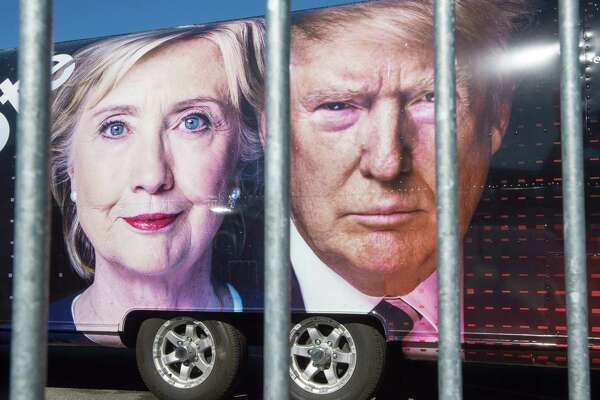 TOPSHOT - Large images of Democratic nominee Hillary Clinton and Republican nominee Donald Trump are seen on a CNN vehicle, behind asecurity fence, on September 24, 2014, at Hofstra University, in Hempsted, New York. The university is the site of the first Presidential debate on September 26, between Democratic nominee Hillary Clinton and Republican nominee Donald Trump. / AFP PHOTO / PAUL J. RICHARDSPAUL J. RICHARDS/AFP/Getty Images