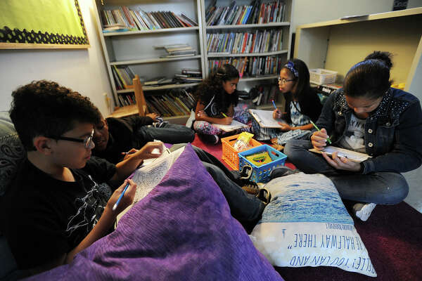 Sixth-graders sit on a rug propped up by oversized pillows, their work illuminated by a small lamp, at New Beginnings Family Academy charter school in Bridgeport on Sept. 13. The school follows a progressive educational model.