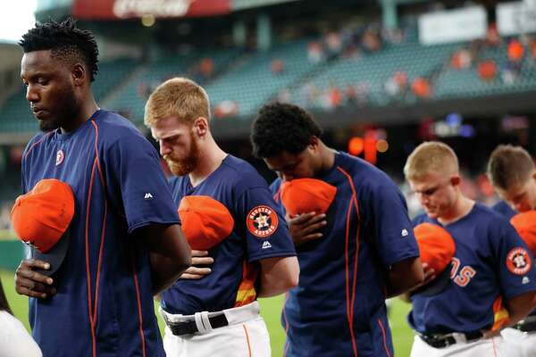 "David Paulino, left, who with his Astros teammates observed a moment of silence, wrote  ""RIP 16"" on his cap in tribute to Jose Fernandez."