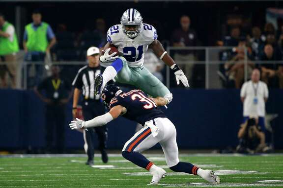 Cowboys running back Ezekiel Elliott leaps over the Bears' Chris Prosinski on his way to completing a 14-yard run in the second half of Sunday night's game.