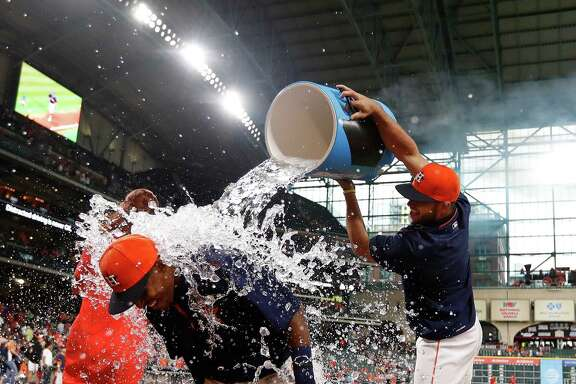 Astros pitcher Lance McCullers gives a soaking to Tony Kemp, who was engaged in a postgame interview after hitting his first major league home run in Sunday's 4-1 Astros victory over the Angels.