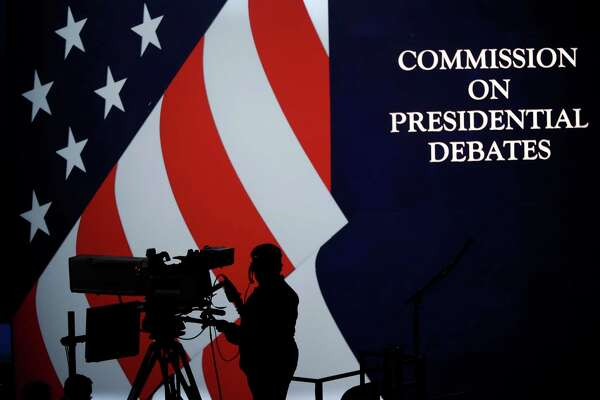 A cameraman is silhouetted against an an American flag during preparations for the presidential debate at Hofstra University in Hempstead, NY, Sunday, Sept. 25, 2016.