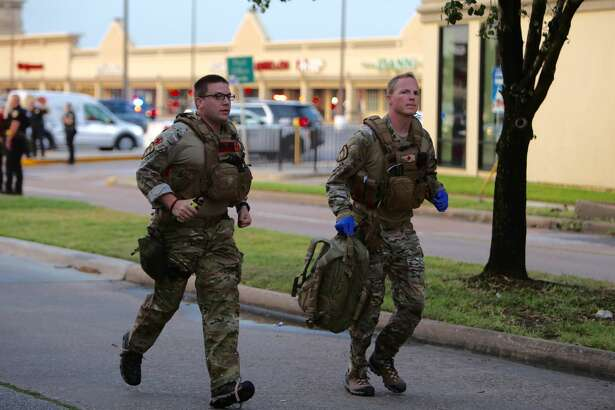 Two law enforcement officials run near a strip mall along Weslayan Street in southwest Houston, Texas on Sept. 26, 2016. A gunman fired shots near that strip mall, striking several people in the area.