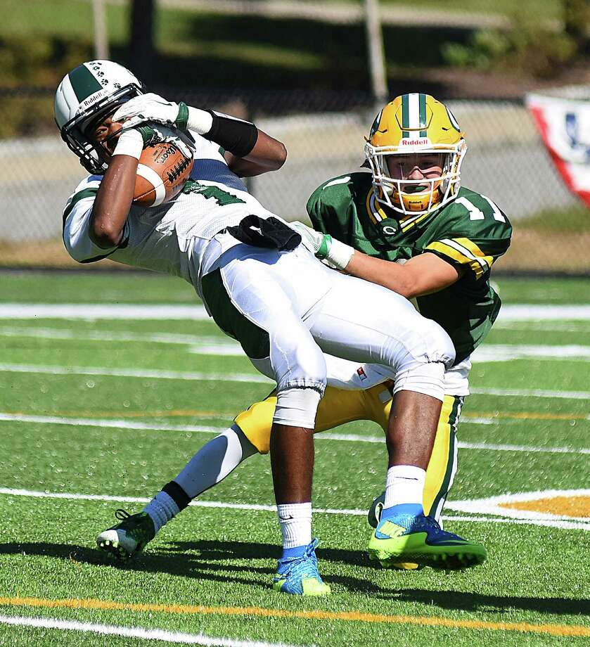 Norwalk wide receiver Jalen Elliott, left, makes an off-balance catch after getting hit by Trinity Catholic's Mike Riddle during Saturday's FCIAC football game at Gaglio Field in Stamford. Photo: John Nash / Hearst Connecticut Media / Norwalk Hour