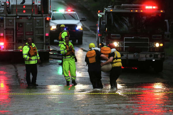 San Antonio firefighters rescue one of five people from a van that was trapped in high water Monday September 26, 2016 on the 13000 block of George Road on San Antonio's Northwest Side after a night of heavy rains.