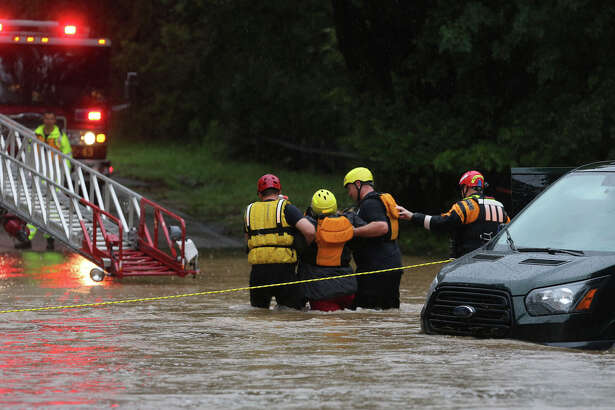 San Antonio firefighters rescue one of five people from a van that was trapped in high water Monday September 26, 2016 on the 13000 block of George Road on San Antonio's Northwest Side after a night of heavy rainfall.