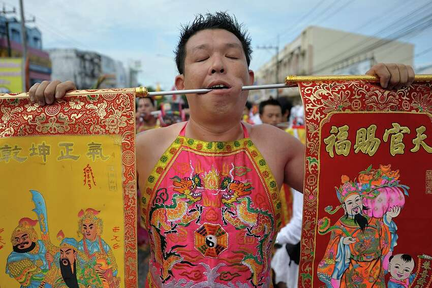 RANONG, THAILAND - 2013/10/11: A Mahsong with a metal rod piercing his cheek takes part in a street procession during the annual Vegetarian Festival in Ranong city. Mahsong are the people who invite the spirits of gods to possess their bodies. (Photo by Atid Kiattisaksiri/LightRocket via Getty Images)