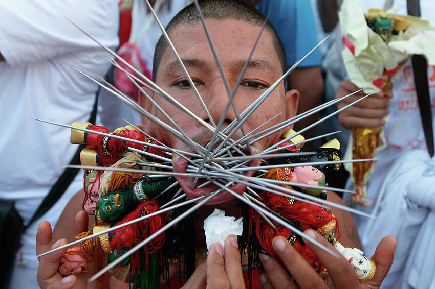 PHUKET, THAILAND - OCTOBER 19: A Ma Song or a spirit medium has his cheeks and lips pierced as he prepares for a street procession at Jui Tui Shrine during the Phuket Vegetarian Festival on October 19, 2015 in Phuket, Thailand. The Phuket Vegetarian Festival, otherwise known as the Nine Emperor Gods Festival is a Taoist celebration which takes place over nine days on the eve of the 9th lunar month of the Chinese calendar. Devotees will observe strict vegetarian diet and perform sacred rituals to purify themselves. (Photo by Suhaimi Abdullah/Getty Images)