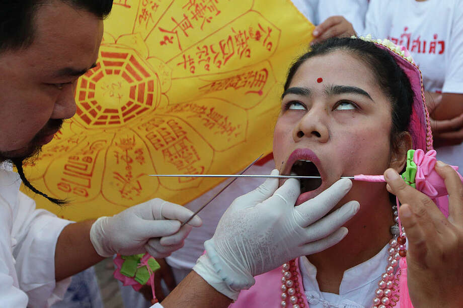 PHUKET, THAILAND - OCTOBER 19:  A Ma Song or a spirit medium has her cheeks pierced as she prepares for a street procession at Jui Tui Shrine during the Phuket Vegetarian Festival on October 19, 2015 in Phuket, Thailand. The Phuket Vegetarian Festival, otherwise known as the Nine Emperor Gods Festival is a Taoist celebration which takes place over nine days on the eve of the 9th lunar month of the Chinese calendar. Devotees will observe strict vegetarian diet and perform sacred rituals to purify themselves.  (Photo by Suhaimi Abdullah/Getty Images) Photo: Suhaimi Abdullah/Getty Images