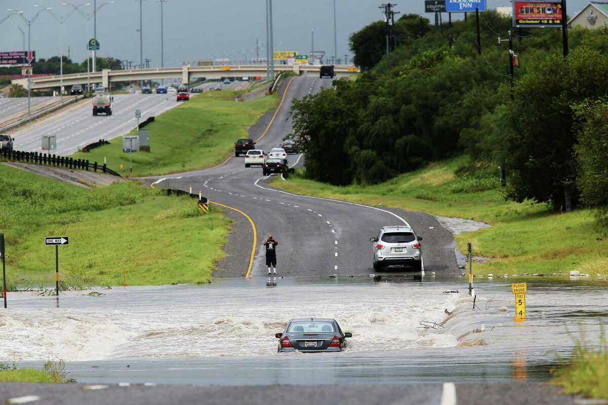 A motorist stops to photograph a car in the floodwaters of Leon Creek by U.S. Highway 90 West, Monday, Sept. 26, 2016. Heavy rains cause flooding throughout San Antonio and the San Antonio Fire Department responded to over 40 water rescues throughout the morning.