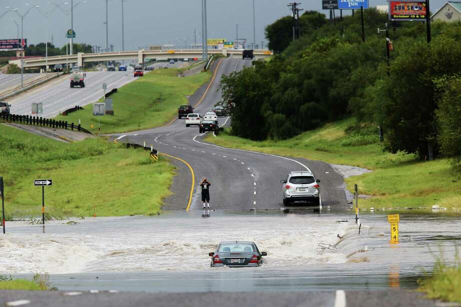 A motorist stops to photograph a car in the floodwaters of Leon Creek by U.S. Highway 90 West, Monday, Sept. 26, 2016.  Heavy rains cause flooding throughout San Antonio and the San Antonio Fire Department responded to over 40 water rescues throughout the morning. Photo: JERRY LARA, San Antonio Express-News / © 2016 San Antonio Express-News