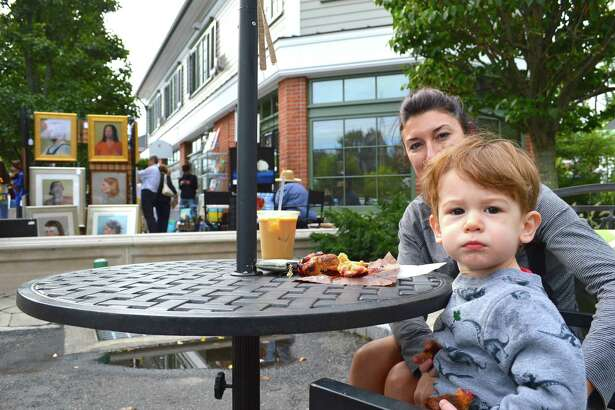 Bridget Lasda of Darien and her son Cameron, 1, take a muffin break at the 2nd annual Artists at Grove Street Plaza event, Saturday, Sept. 24, 2016, in Darien, Conn.