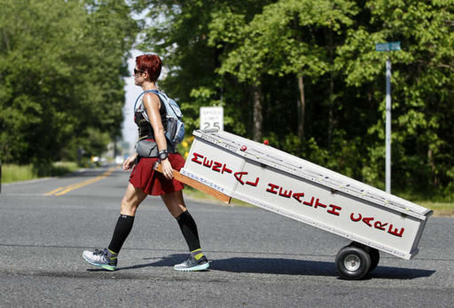 Greta Schwartz, of Seaville, N.J., is dressed like a Spartan warrior pulling a casket as she walks along route 206, from southern New Jersey to Trenton Tuesday, May 31, 2016, in Tabernacle, N.J. Schwartz, who got the idea for the walk after attending a discussion on mental health, addiction and suicide from former U.S. Rep. Patrick Kennedy last year, hopes to arrive at the Statehouse on Wednesday. (AP Photo/Mel Evans) Photo: Mel Evans