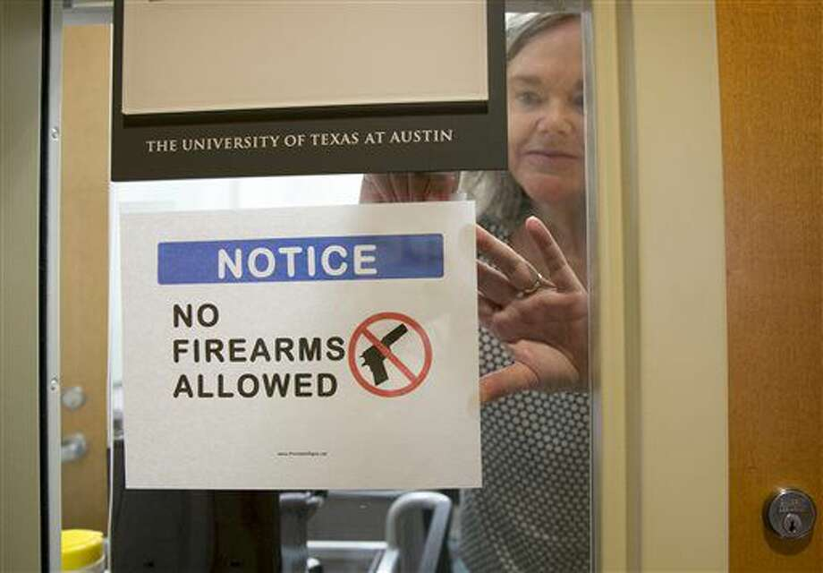 University of Texas at Austin Anthropology professor Pauline Strong posts a sign prohibiting guns at her office on the first day of the new campus-carry law Monday, Aug. 1, 2016. The law pushed by Gov. Greg Abbott and the Republican legislative majority will make Texas one of a handful of states that guarantee the right to carry concealed handguns on campus. (Jay Jenner/Austin American-Statesmanvia AP) Photo: Jay Janner