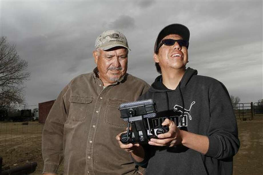 In this April 8, 2016 photo, Gary Clark watches his grandson Jayvion Chee fly a drone, at Clark's farm in Shiprock, N.M. (Jon Austria /The Daily Times via AP) MANDATORY CREDIT Photo: Jon Austria