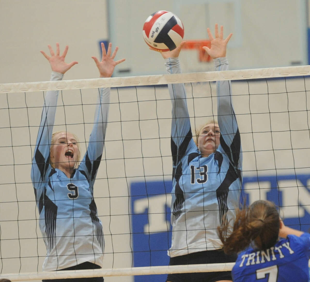 Greenwood's Kailey Martinez (9) and Kyndall Dove (13) go up for a block against Trinity's Kinzie Roemer (7) on Tuesday, Sept. 6, 2016, at Trinity. James Durbin/Reporter-Telegram