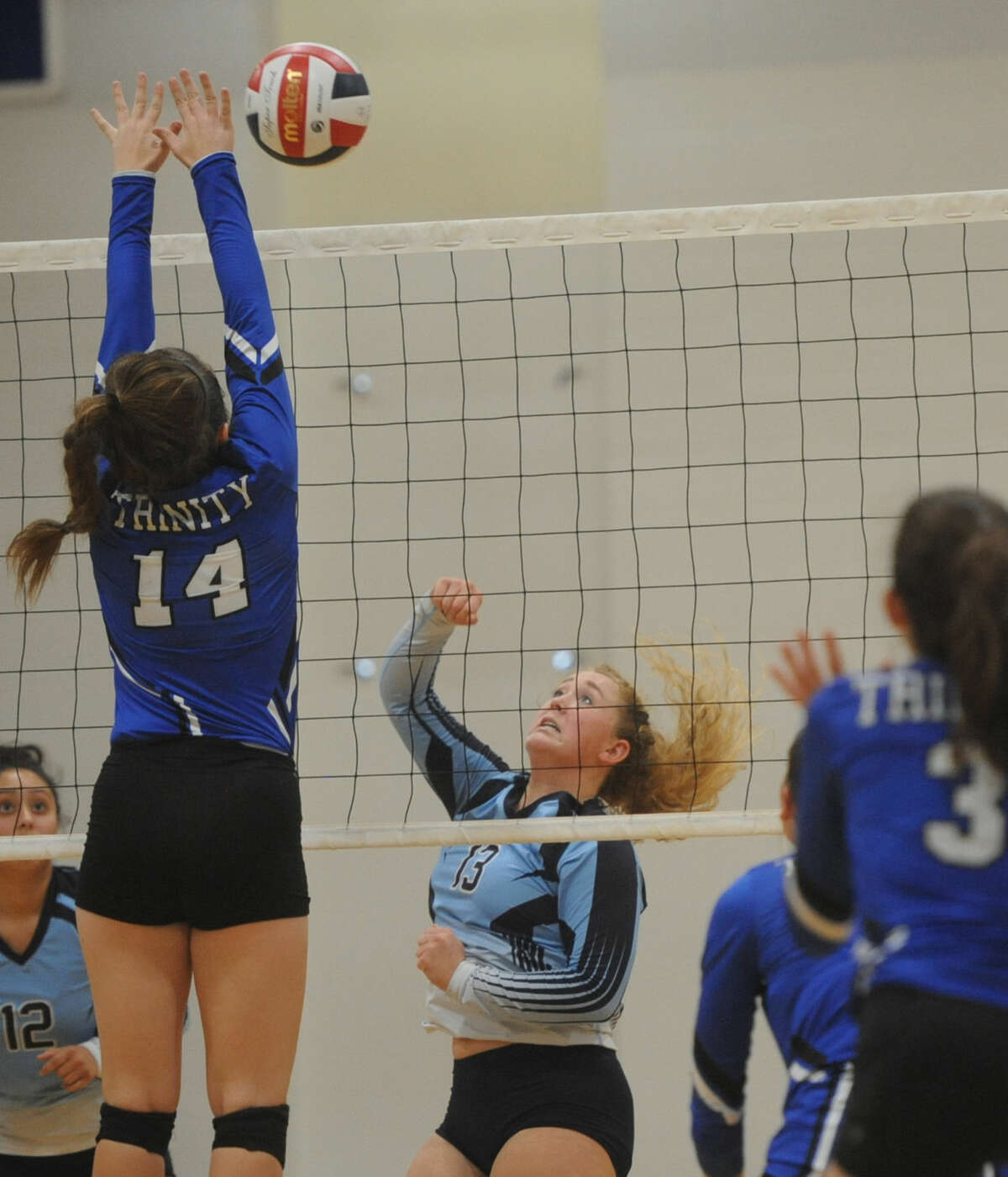 Trinity's Rebecca Young (14) tries to block a hit from Greenwood's Kyndall Dove (13) on Tuesday, Sept. 6, 2016, at Trinity. James Durbin/Reporter-Telegram