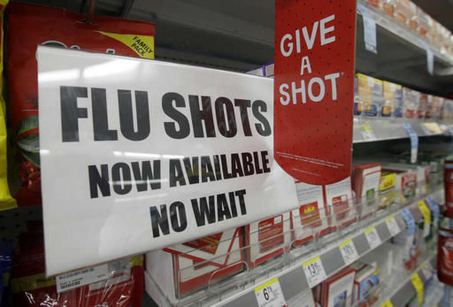 FILE - In this Sept. 16, 2014 file photo, a sign telling customers that they can get a flu shot in a Walgreen store is seen in Indianapolis. Kids may get more of a sting from flu vaccination this fall: Doctors are gearing up to give shots only, because U.S. health officials say the easy-to-use nasal spray version of the vaccine isn't working as well as a jab. Needle-phobic adults still have some less painful options. But FluMist, with its squirt into each nostril, was the only ouch-free alternative for children, and has accounted for about a third of pediatric flu vaccinations in recent years. (AP Photo/Darron Cummings, File) Photo: Darron Cummings