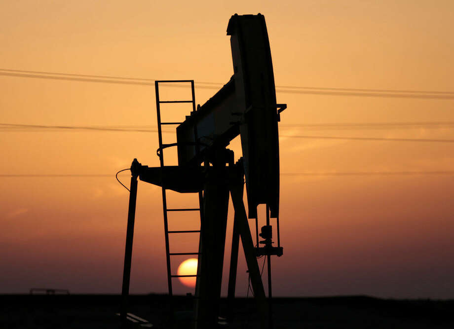FILE: An oil pump works at sunset on Saturday, April 16, 2016, in the desert oil fields of Sakhir, Bahrain. Oil-producing countries are to meet in Qatar on Sunday, April 17, 2016, to discuss a plan to freeze output but their gathering comes as nations like Iran rapidly ramp up their pumping. (AP Photo/Hasan Jamali)