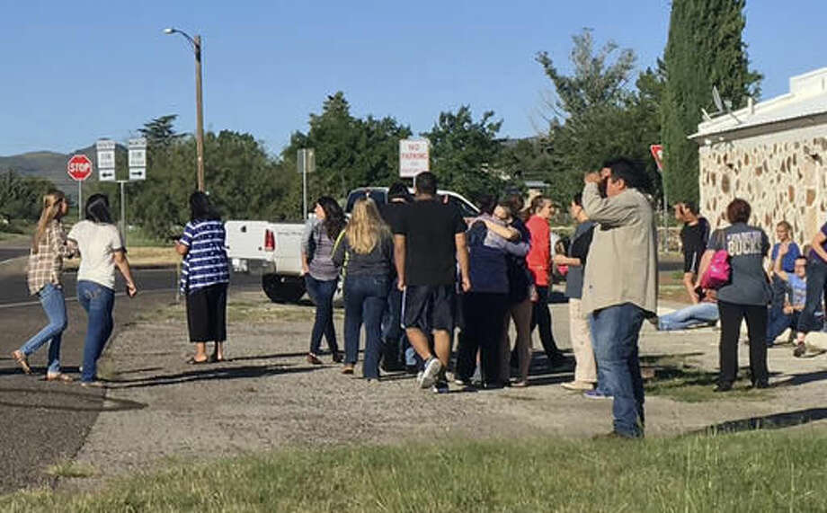 In this photo provided by the Alpine Avalanche, people gather near the Alpine High School school campus after a shooting, in Alpine, Texas, Thursday, Sept. 8, 2016. A student died of an apparent self-inflicted gunshot wound, the Brewster County sheriff said. (Gail Yovanovich/Alpine Avalanche via AP) Photo: Gail Yovanovich